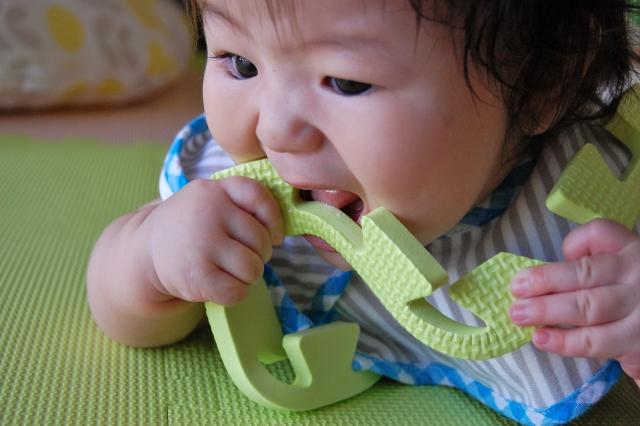 マットを噛む赤ちゃん
