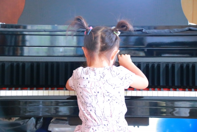 ピアノの前に座る幼児
