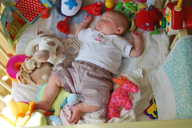 オモチャに囲まれて寝る赤ちゃん