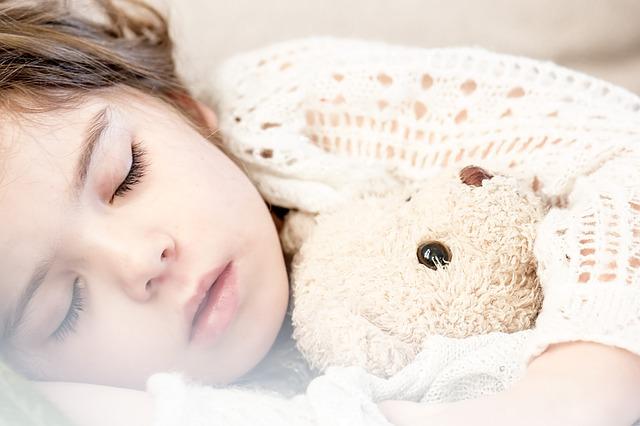 ぬいぐるみを抱いて寝る子供